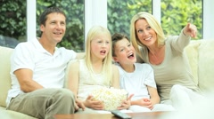 Young Family Watching Movie Together with Popcorn Stock Footage