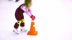 Little girl skates on ice rink helps herself by holding props Stock Footage