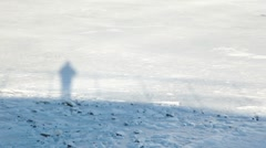 Moving shadow on snow man stand on deck Stock Footage