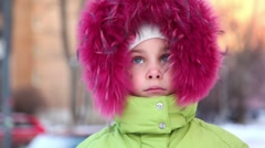 Little girl in fur hood buttoned at collar, look at camera Stock Footage