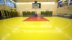 Inside lighted school gym hall with red yellow floor and basket, upward motion Stock Footage