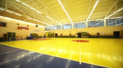 Lighted school gym hall with red yellow floor and baskets - stock footage