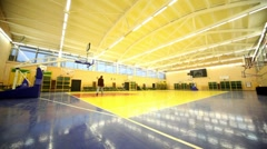 Man walk and turn off light inside school gym hall Stock Footage