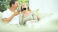 Attractive Couple Relaxing at Home Drinking Wine Stock Footage