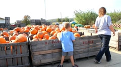 Mom and son picking out a pumpkin Stock Footage