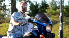 Man on his Motorcycle pulling out of driveway. Stock Footage