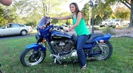 Beautiful brunette posing on a Harley Davidson motorcycle. Stock Footage