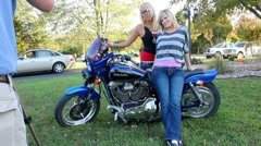 2 Beautiful blonde girls posing with a Harley Davidson motorcycle Stock Footage