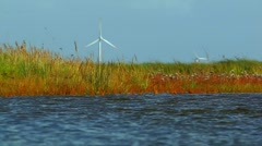 Wind engines behind swamp, intertidal mudflats, Borkum, North Sea, Germany Stock Footage
