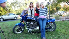 3 gorgeous women posing for photos on a Harley Davidson motorcycle Stock Footage