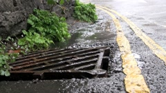 Rain Water Running Down into Road Gutter Drain Stock Footage