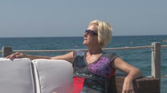 Woman lounging at the sea, CU Stock Footage