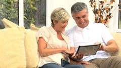 Middle Aged Couple Using Wireless Tablet Stock Footage