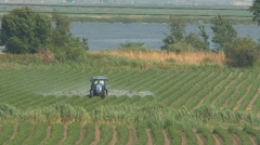 Tractor spraying pesticide on field Stock Footage