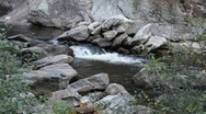 Water gently flowing in a stream over large rocks Stock Footage