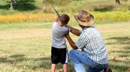 Stock Video Footage of (Father/Son) Man helping child learn to shoot a shotgun
