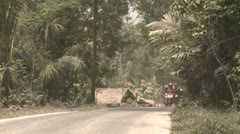 Motorbikes Drive Along Road Covered In Volcanic Ash Stock Footage