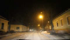 Driving at night through a snow covered village in Lower Austria Stock Footage
