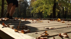 Jogging man on wooden bridge covered with fallen leaves 2 Stock Footage