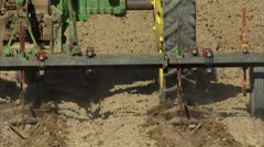 Tractor implement working ground behind CU - stock footage