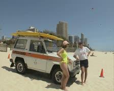 Lifeguard talking on beach Stock Footage