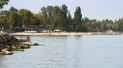Lake Garda with beach and senior fisherman Stock Footage