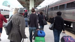 Crowd of Amtrak train travelers on platform walking - no faces visible Stock Footage