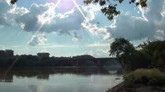 Jet high over river, framed by sun flare. Washington, DC Stock Footage