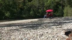 Couple sitting by river on gravel beach Stock Footage