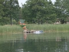 Lake shore and holidaymaker on it filmed from the motor boat. Stock Footage