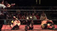 Pro wrestling tag match - double team leg sweep - stock footage
