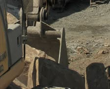 Backhoe or excavator placing large stone in a trench. Construction. Stock Footage