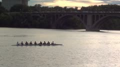 Rowers into sunset while commuters drive home Stock Footage