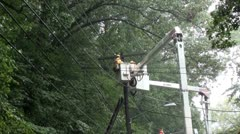 Two linemen hammer at electric pole from cherry pickers, rain. Stock Footage