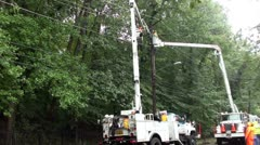 Linemen working in rain, from two trucks, wide shot. Stock Footage