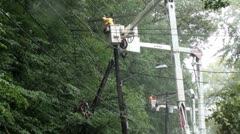 4 linemen in 4 buckets repair power line in rain. - stock footage