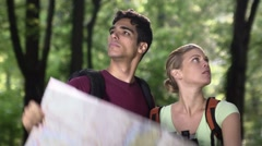 Young couple looking at map during trek after losing orientation Stock Footage