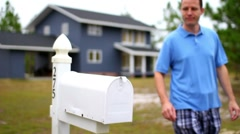 Stock Video Footage of A Man Checks his Mail Outside House at his Mailbox
