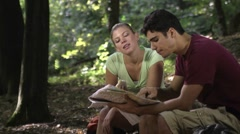 Man and woman looking at map and eating snack after hiking Stock Footage