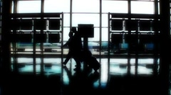 Silhouettes of two travelers, men, passing in airport Stock Footage