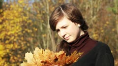 Teen girl holding a bunch of leaves in autumn park Stock Footage