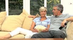 Mature Caucasian Couple Enjoying TV & Popcorn Stock Footage