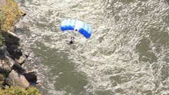 Base Jumper floating down towards river Stock Footage
