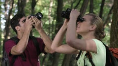 Young people doing birdwatching in forest Stock Footage