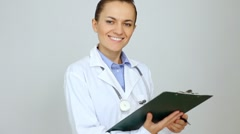 Happy female doctor with clipboard over grey background HD - stock footage