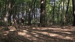 Boy and girl trekking in forest - stock footage