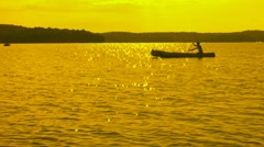 Golden canoeist goes by. Stock Footage