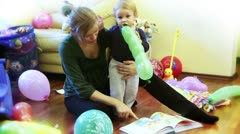 Mother and baby boy reading stories, surrounded with toys Stock Footage
