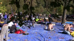 Base jumpers repacking their parachutes on blue tarp - stock footage