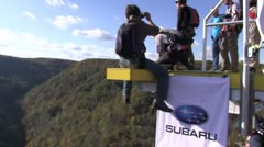 Base jumper leaps from platform on bridge as others watch Stock Footage